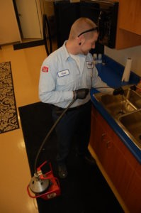 Bill Howe Drain Technician, Nate Thorson, snaking out a kitchen drain
