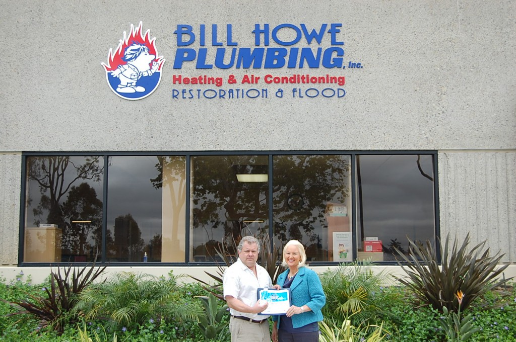Mark Card and Tina Howe in Front of Bill Howe Plumbing with new award